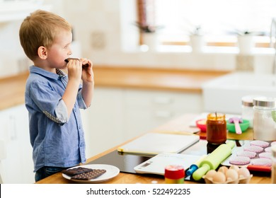 Child tasting chocolate bar in kitchen which is ingredient to cookies