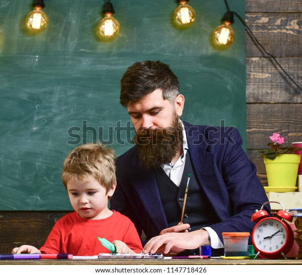 Child and teacher on busy faces painting, drawing. Teacher with beard, father and little son in classroom while drawing, creating, chalkboard on background. Drawing lesson concept.