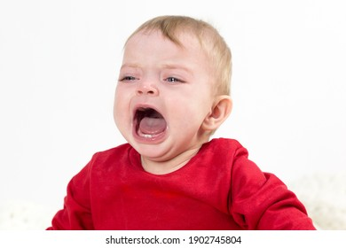A child with tears in his eyes is crying loudly with his mouth wide open.