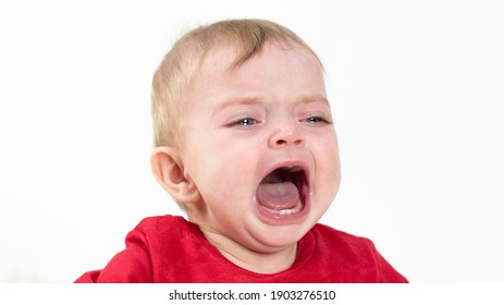 A child with tears his eyes is crying loudly with his mouth wide open.