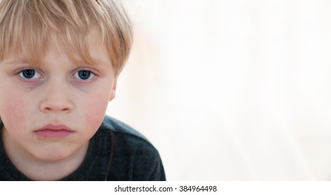 Child with tears on cheek