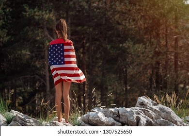 Child teenager girl at nature background with an American flag on her shoulders. USA resident, US citizen. Immigration concept