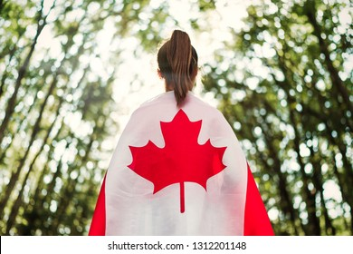 Child teenager girl at nature background an Canada flag on her shoulders