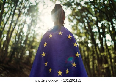 Child teenager girl at nature background an European Union flag on her shoulders