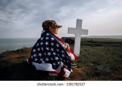 child teenager wrapped in an American flag sits on the grass near the grave of his father, a soldier hero of America