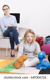 Child therapist observing how child girl interacts with toys