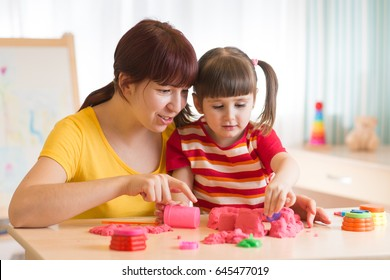 Child with therapist playing with toy the sand. Psychologist works, sand therapy