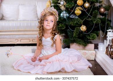 child thinking near the Christmas tree on Christmas morning