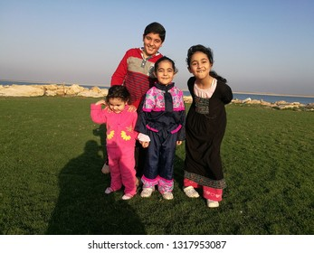 A child and three girls stand outdoors on the seashore in Jubail Industrial City, Saudi Arabia in the summer of 2018