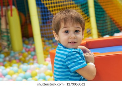 child of three years old is playing in a ball pool. boy smiling spends fun time in the children's room