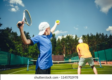 Child throwing ball and gesticulating racquet while having game on court with male athlete