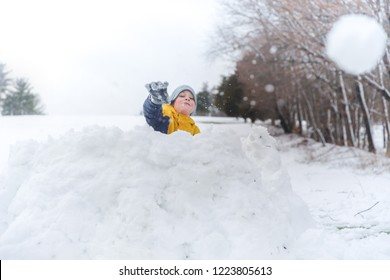 the child throws snowball. the boy playing in snow fort. The concept of winter fun outdoors. Copy space for your text