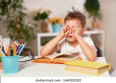 the child is tired of learning. home schooling, homework. the boy rubs his eyes from fatigue reading books and textbooks. a little boy student sitting at a table with books. vision problems