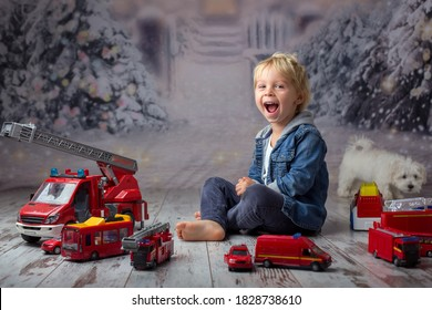 Child, toddler blond boy, playing with fire trucks on the floor at home