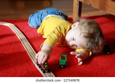 Child, toddler boy, playing at home with trains and tracks