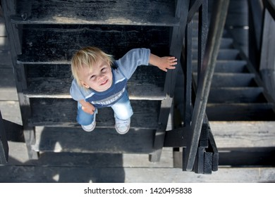 Child, toddler boy, sitting on wooden stairs, outdoor