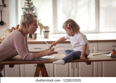 child Toddler with Down syndrome is studying the letters of the alphabet along with the teacher, the real interior. Concept children with special need and their development.
