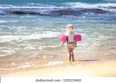 Child toddler girl in swimwear on beach standing in front of storming sea and ready to swim in during summer vacation concept fear children water safety