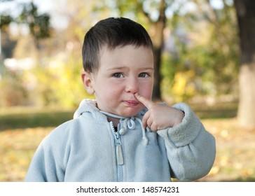 Child toddler picking up his nose.