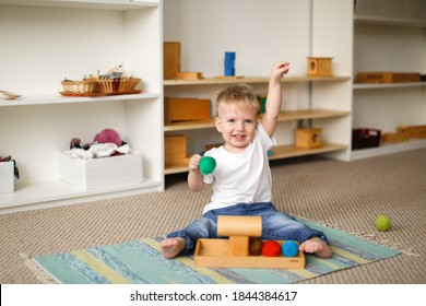 child toddler plays with balls and cylinders, developing sensory activities in montessori and earlier development of children, independence of babies