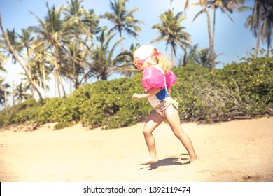 Child toddler running in swimwear on beach with bright sunlight during summer vacation concept happy childhood travel lifestyle