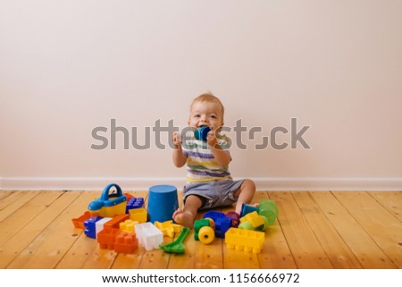 330e443dd Child, toddler with smiling face plays with brick constructions. Boy spends  fun time in