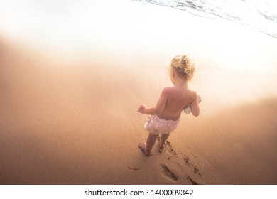 Child toddler standing hesitated on beach in front of sea and going to swim concept children overcoming fear water