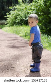 Child toddler standing on a path in park with shy or lost expression.