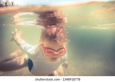 Child toddler swimming underwater during summer beach holidays vacation