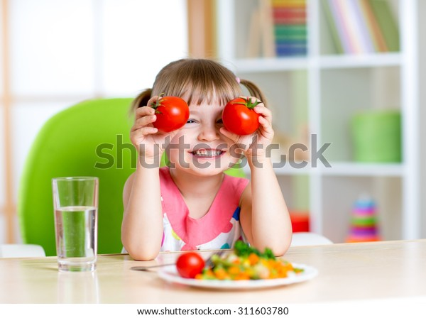 Child with tomatoes. Happy little girl with vegetables at home.
