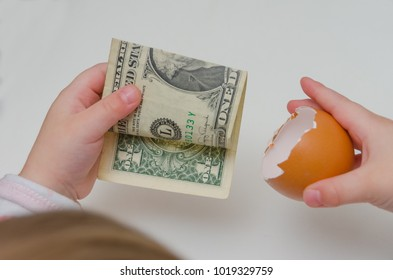 a child took a dollar in an egg shell on white background