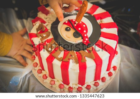 Child Touching Pirate Themed Birthday Cake Closeup Of Red And White Black Kids