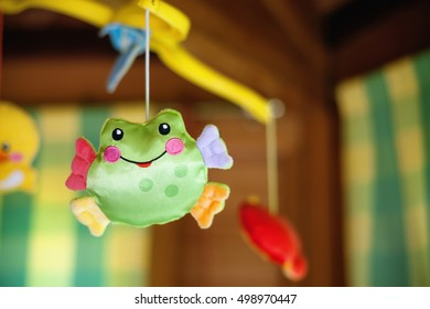 Child toy with frog hanging on baby cradle