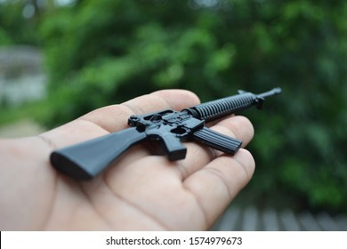 Child toy gun model. M16 small gun placed in the palm of the hand