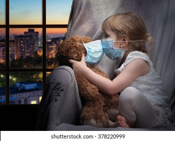 A child and a toy in a medical mask. The girl kisses a bear through the mask. House, evening, outside the city. Conceptually about diseases, infection and allergy