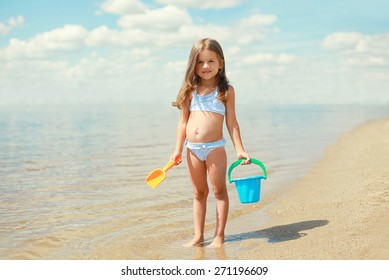 Child with toys and having fun on the beach near sea in summer sunny day
