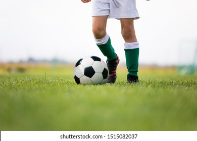 Child training soccer on fresh grass pitch. Soccer camp for kids. Boys practice dribbling in a field. Player develop dribbling skills. Boy in yellow shirt training with ball