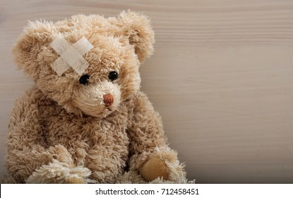 Child trauma concept.Teddy bear with bandage on head sitting on a wooden background. Copy space