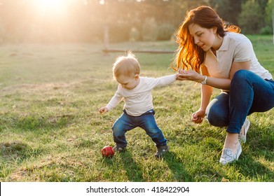 The child tries to pick an apple from the ground. Mother holds his hand. Happy family walking outdoor