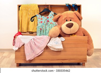 Child trunk with a big teddy bear and girl dresses. Chest with toys and clothes.