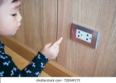 A child is trying to poke into electrical outlets. Kid with electrical socket.