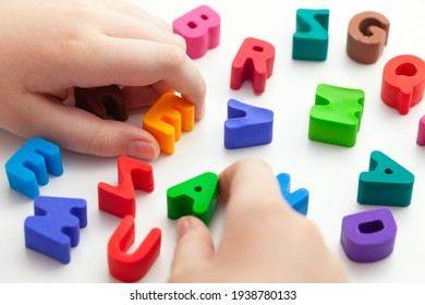 A child trying to spell a word with letters. Shallow depth of field. Close up.