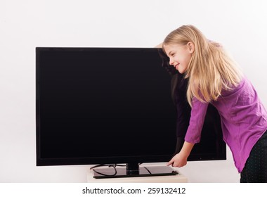 Child TV addiction example -  Cute girl hugging the tv in front of a white background