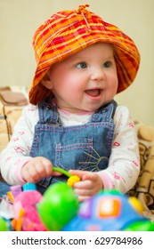 the child is two years old, laughing, bright clothes