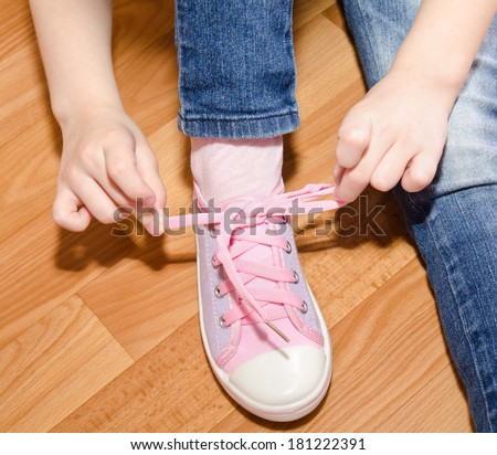 Child tying her shoes sitting on the floor at home closeup
