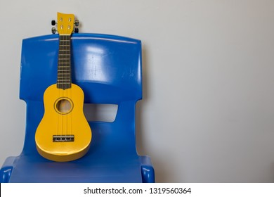 Child ukulele on chair. School music lesson practice room. Bright yellow uke on blue plastic chair. Childrens musical instrument.
