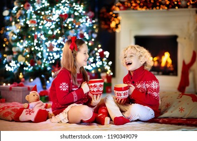 Child under Christmas tree at home. Little boy and girl in knitted sweater with Xmas ornament drink hot chocolate. Family with kids celebrate winter holidays. Kids open presents at fireplace.