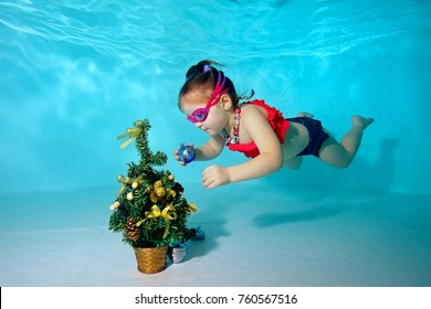 Child underwater in the pool decorates the Christmas tree with Christmas toys. Portrait. Shooting under water. Horizontal orientation