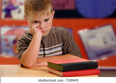 Child with unhappy expression at school desk
