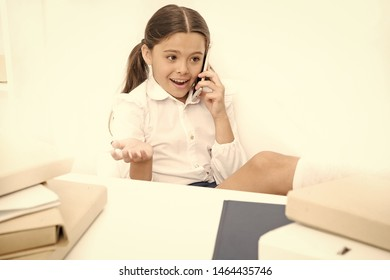 Child use smartphone mobile to communicate in school. Fresh school gossip. She like talking too much. Discussing rumors. Cute gossip girl. Schoolgirl smiling face discuss fresh gossips with mates.